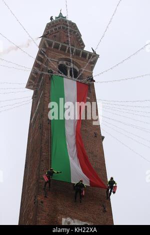 Vicenza, VI, Italia - 4 de diciembre de 2015: Los bomberos con una gran bandera italiana y la torre del antiguo palacio llamado Basilica Palladiana
