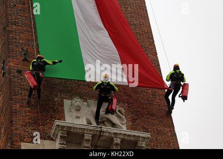 Vicenza, VI, Italia - 4 de diciembre de 2015: Los bomberos con una gran bandera italiana y la torre de un palacio llamado Basilica Palladiana durante un ejercicio