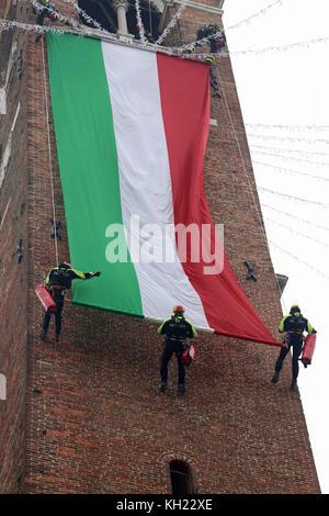 Vicenza, VI, Italia - 4 de diciembre de 2015: Los bomberos con una gran bandera italiana y la torre del antiguo palacio llamado Basilica Palladiana durante una exerc