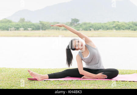 Mujer joven asiática haciendo la práctica del yoga en el parque de la salud antecedentes - concepto de vida sana y equilibrio natural entre el cuerpo y el desarrollo mental