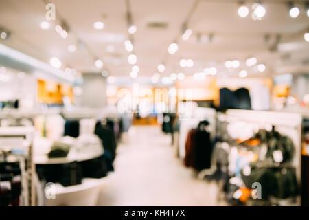 Bokeh blured vista de ropa en estantes y colgador en la tienda del centro comercial.