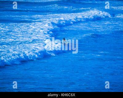 Imagen tratada / estilizadas de surfista en Newquay en Cornualles. Las olas realmente fuera de la playa Fistral. Foto de stock