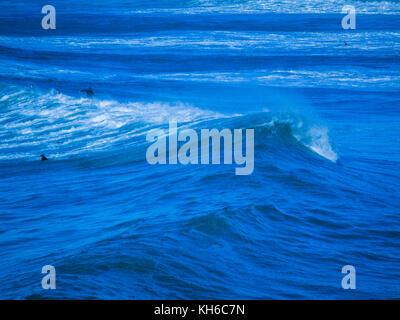 / Estilizada imagen tratada de surfistas en Newquay en Cornualles. Las olas realmente fuera de la playa Fistral. Foto de stock