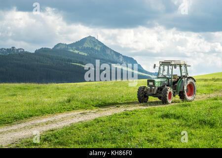 Tractor viejo en pradera. hermosa vista a la montaña en los Alpes