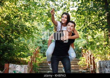 Joven pareja feliz disfrutando piggyback paseo en el parque al aire libre, mujer sonriente dedo señalador lejos