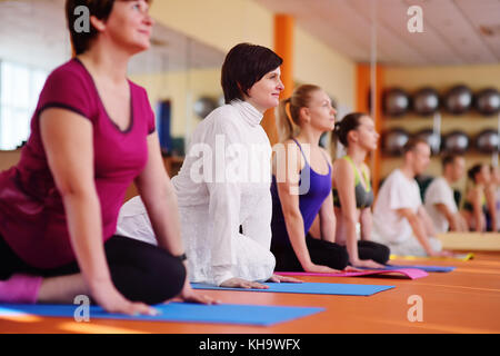 Mujer 40s metida en yoga en el gimnasio estilo de vida activo.