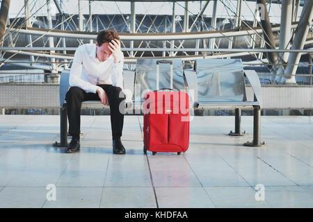 Retraso en el vuelo o un problema en el aeropuerto, cansado desesperada esperando en la terminal de pasajeros con maleta