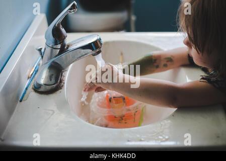 Un niño niña pintura lavado las manos en un lavabo del baño.