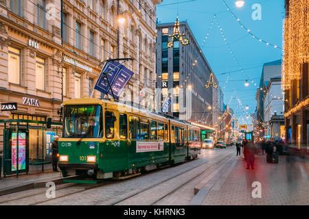 Helsinki, Finlandia - Diciembre 8, 2016: El tranvía sale desde una parada en la calle aleksanterinkatu. vista nocturna Foto de stock