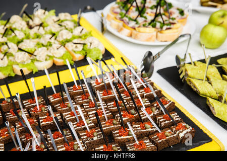 Tartaletas, bruschetta o canapés en una bandeja en un restaurante. Aperitivos. mesa de buffet restaurante feed Año Nuevo Navidad Foto de stock