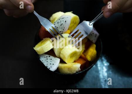 Tazón de fruta fresca ensalada saludable sobre fondo de madera. hombre comiendo con dos horquillas.