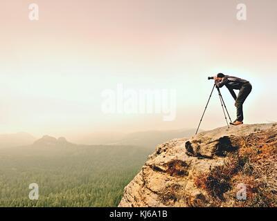 Fotógrafo profesional toma fotos de misty paisaje con espejo y un trípode de cámara. Una espesa niebla en paisaje otoñal. El hombre de trabajo sobre sharp clif.
