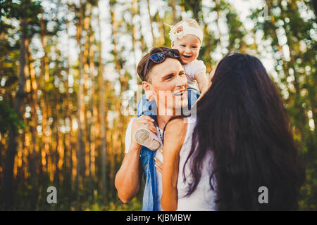 Elegante joven familia de mamá, papá e hija de un año de edad rubio sentado cerca de padre en los hombros, al aire libre fuera de la ciudad en un parque en medio de árboles altos en verano al atardecer.