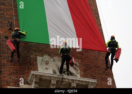 Vicenza, VI, Italia - 4 de diciembre de 2015: Los bomberos con una gran bandera italiana en un antiguo palacio llamado Basilica Palladiana durante un ejercicio