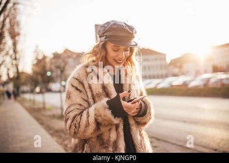 Hermosa niña sonriente y mensajes de texto en su celular en las calles de la ciudad Foto de stock