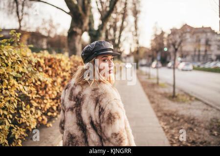 Hermosa niña vistiendo pieles y montando su bicicleta en las calles de la ciudad Foto de stock
