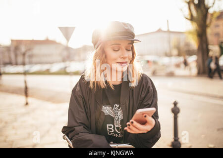 Hermosa niña escribir mensajes de texto en su celular en las calles de la ciudad Foto de stock