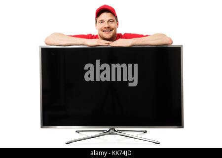 Vendedor sonriente en rojo uniforme sobre gran pantalla de tv en blanco aislado sobre fondo blanco.