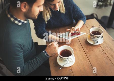 Joven pareja atractiva con tablet en la cafetería. Foto de stock