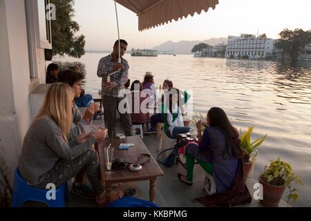 Los clientes sentados en la terraza junto al lago, en Jheel's Ginger Café Bar & Bakery, por Chandpol, Udaipur, Rajasthan, India Foto de stock