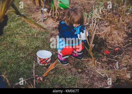 Los niños ayudan a su abuelo cavar en el jardín durante los meses de invierno