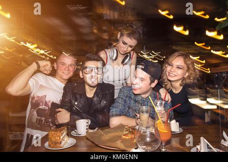 Amigos divirtiéndose y bebiendo cerveza en el club nocturno de larga exposición.