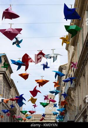 Molinetes de plástico decorativo en varios colores suspendidos de cables entre los edificios a lo largo de una estrecha calle en Arles. una torre del reloj es visto en el di
