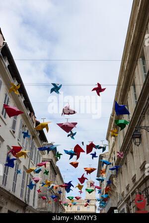 Toda la pantalla de plástico decorativo molinetes en varios colores suspendidos de cables entre los edificios a lo largo de una estrecha calle en Arles. Un reloj t