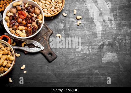 Nueces y frutos secos en un recipiente con un cascanueces. sobre una pizarra negra.