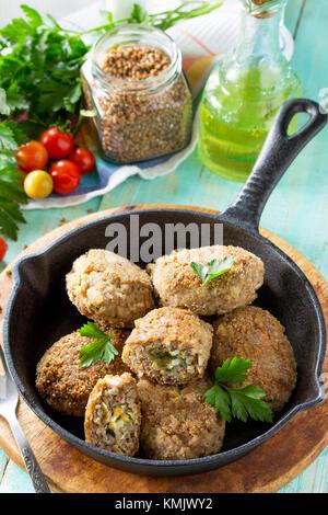 Albóndigas caseras con trigo sarraceno y huevo relleno. Sartén de hierro fundido con deliciosos fritos croquetas, las hierbas frescas y verduras en la mesa de la cocina