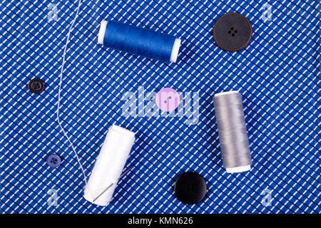 Elementos para coser ropa. Cosiendo botones, los carretes de hilo y telas. Vista superior