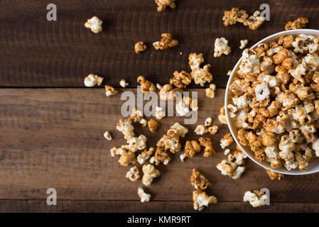 Palomitas de caramelo en el fondo de la tabla de madera. con sabor a caramelo en un tazón de palomitas de maíz