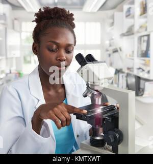 Mujer afroamericana científico, estudiante o técnico en Bata de laboratorio trabaja en un moderno laboratorio con microscopio