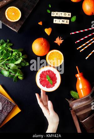Detox fresco jugo de frutas cítricas sobre fondo negro flay sentar Foto de stock