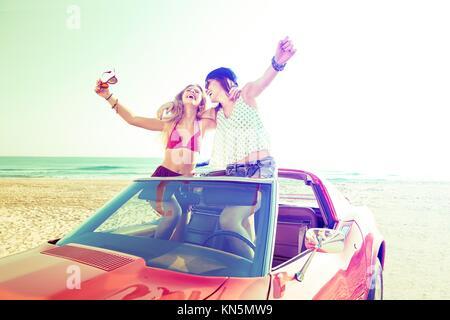Hermosa fiesta amigo chicas bailando en un coche en la playa feliz.