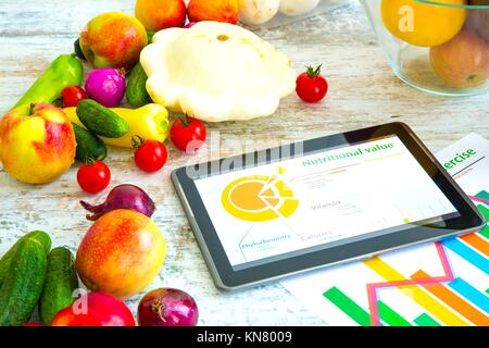 Los alimentos orgánicos y un Tablet PC que muestra información acerca de la nutrición saludable y la composición fitoquímica.