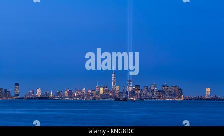 La Ciudad de Nueva York con rascacielos y dos vigas del tributo a la luz. Lower Manhattan, el distrito financiero, el puerto de Nueva York Foto de stock