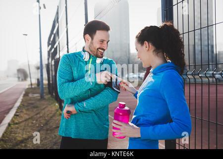 Deportista y sportswoman coqueteo outdoor fitness después de desempeño
