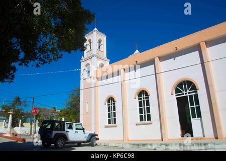 Una iglesia católica muy simple de color durazno en un pequeño pueblo cerca de Cabo San Lucas. Gran puerta lateral se abre y un blanco moderno y flamante Jeep es