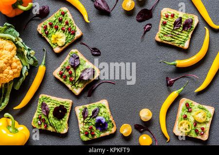 Desayuno diferentes sandwich de aguacate. Diferentes colores frescos vegetales orgánicos. saludable comida vegana cruda sobre fondo gris.