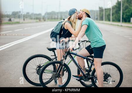 Hermosa pareja joven en amor caminando con bicicletas, besos y abrazos