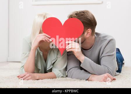 Pareja besándose detrás de forma Corazón