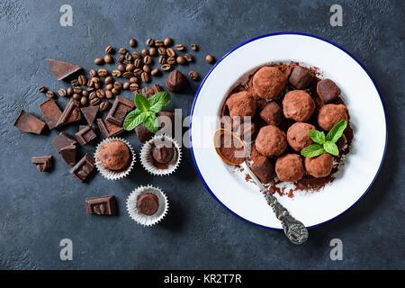 Caseros trufas de chocolate oscuro enrollado en el polvo de cacao y granos de café sobre azul de fondo concreta. Vista superior