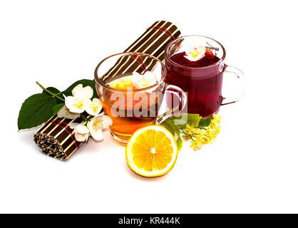 Dos jarras transparentes con bebidas, una alfombra de flores y una rama con hojas