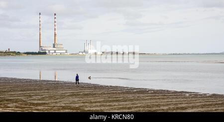 Una persona y su perro a pasear a lo largo de ZPE de Sandymount Strand playa en la Bahía de Dublín, con el emblemático Foto de stock