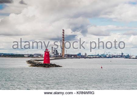 Poolbeg faro en la desembocadura del río Liffey, con las chimeneas de Pololbeg estación generadora de Dublín y el Foto de stock
