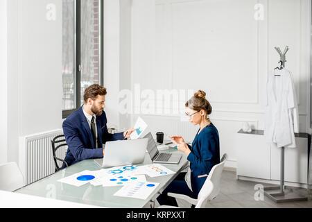 Los gerentes analítica en la oficina de trabajo en equipo.