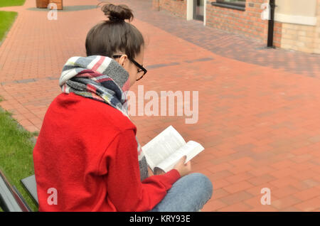 Una niña de gafas con cabello reunidos sentados en el banquillo en la calle y leer un libro. Vista trasera