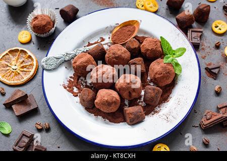 Caseros trufas de chocolate oscuro en la placa blanca decorada con hojas de menta. Composición horizontal