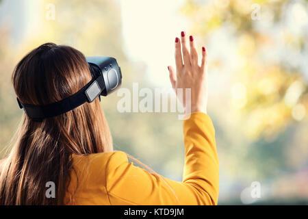 Pretty girl usando auriculares VR fuera en el parque divirtiéndose